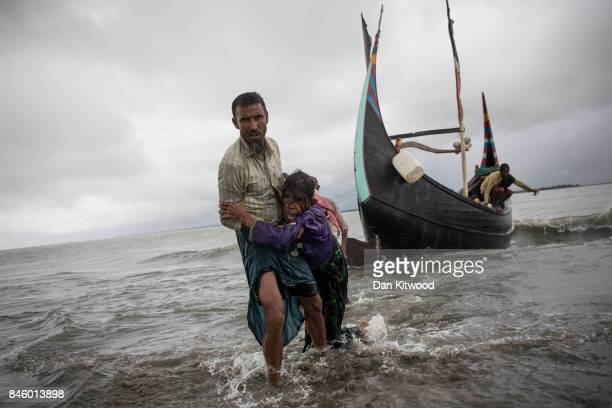 Rohingya man carries an elderly woman after the wooden boat they were travelling on from Myanmar which can be seen in the background crashed into the...
