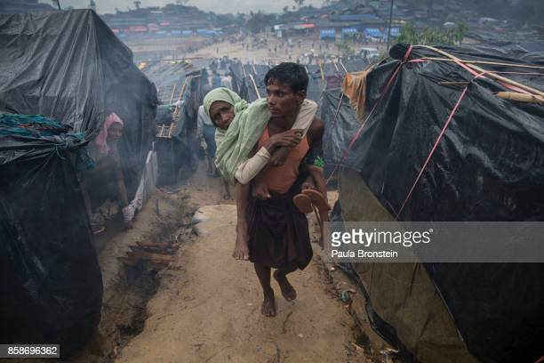 Rohingya man carries his handicapped mother to her tent October 7 Thainkhali camp Cox's Bazar Bangladesh Well over half a million Rohingya refugees...