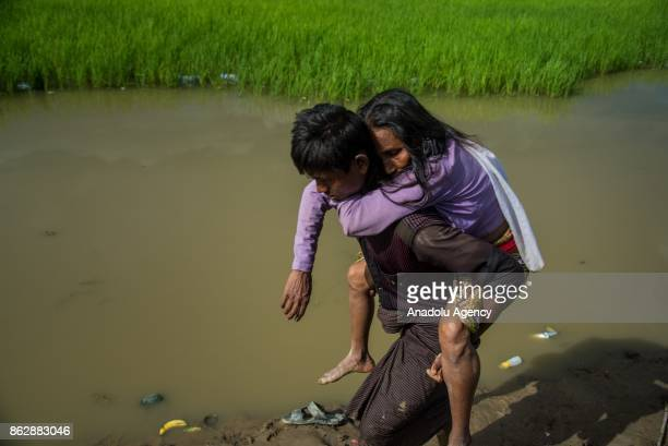 COX'S BAZAR BANGLADESH OCTOBER 17 A Rohingya man fled from ongoing military operations in Myanmars Rakhine state carries an elderly woman while they...
