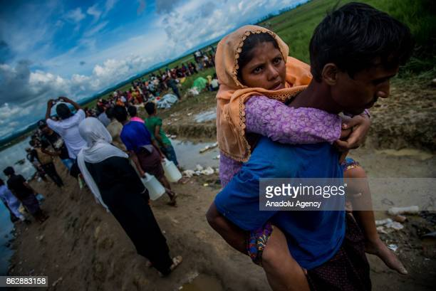 COX'S BAZAR BANGLADESH OCTOBER 17 A Rohingya man fled from ongoing military operations in Myanmars Rakhine state carries a woman while they are...