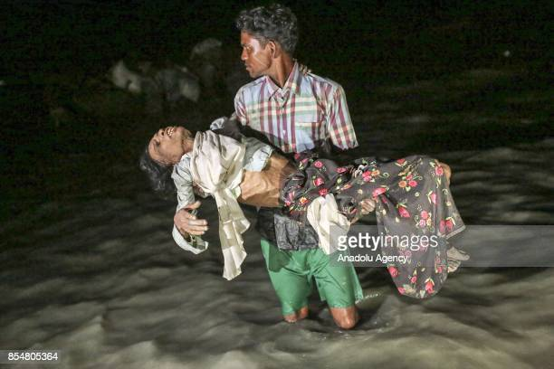 Rohingya man fled with others from oppression within ongoing military operations in Myanmars Rakhine state carries a woman in bad health condition as...