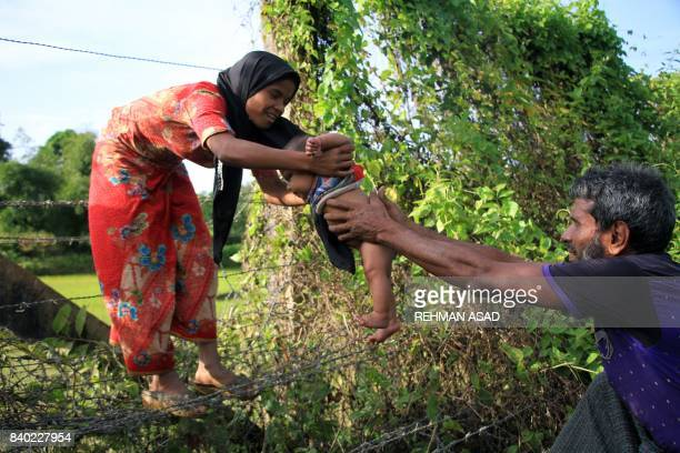 Rohingya man passes a child through a barbed wire border fence near Maungdaw on the border with Bangladesh on August 28 2017 Rohingya refugees in...