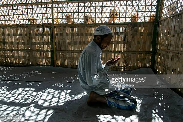 Rohingya man prays inside a makeshift mosque during Friday prayers at an internally displaced persons camp November 23 2012 on the outskirts of...