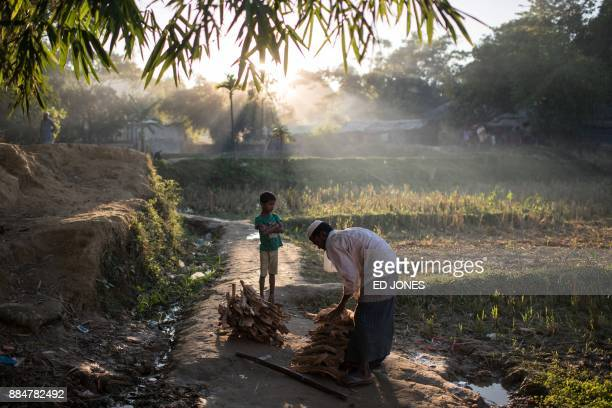 Rohingya man ties wood together at the Naybara refugee camp in Cox's Bazar on December 3 2017 Rohingya are still fleeing into Bangladesh even after...