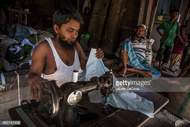 Rohingya man who has worked as a tailor for 25 years mends clothes for his community at the Thet Kay Pyin market on May 17 2016 in Sittwe Burma After...