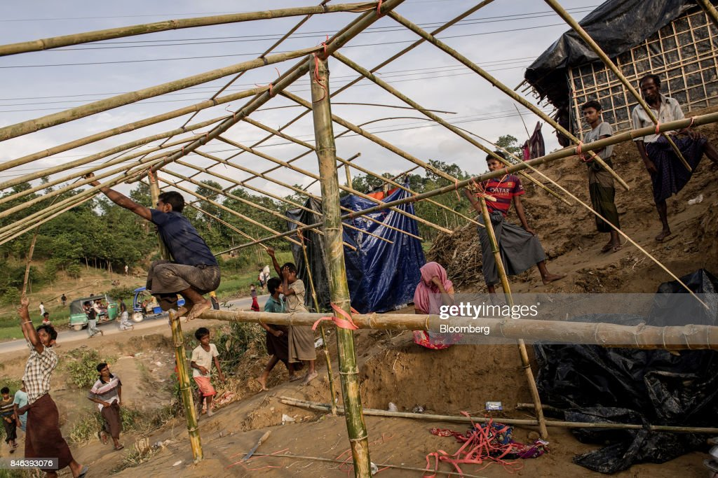 Rohingya men build a hut at a newly set-up refugee camp at Balukhali in Cox's Bazar, Bangladesh, on Tuesday, Sept. 12, 2017. Myanmar's leaderAung San Suu Kyiis under attack over her response to a fresh round of violence that has seen more than 145,000minorityRohingyaMuslims flee into neighboring Bangladesh since last month. Photographer: Ismail Ferdous/Bloomberg via Getty Images