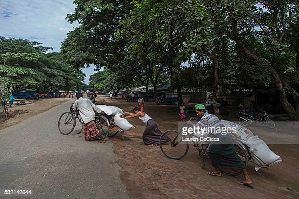 Rohingya men prepare to deliver rice donations from the World Food Program in a storage facility at the Thet Kay Pyin market on May 18 2016 in Sittwe...