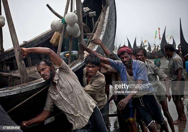 Rohingya men push a fishing boat to shore July 4 2015 in Shamlapur Bangladesh In the past months thousands of Rohingya have landed on the shores of...