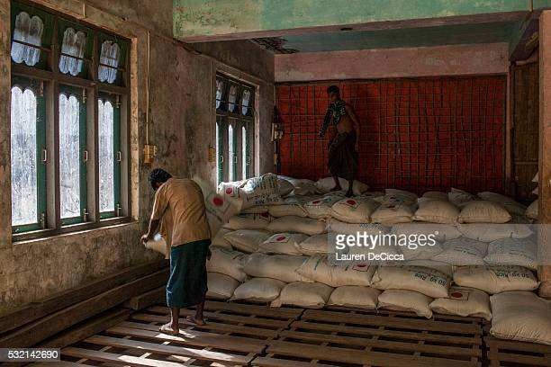 Rohingya men stack rice donations from the World Food Program in a storage facility at the Thet Kay Pyin market on May 17, 2016 in Sittwe, Burma....