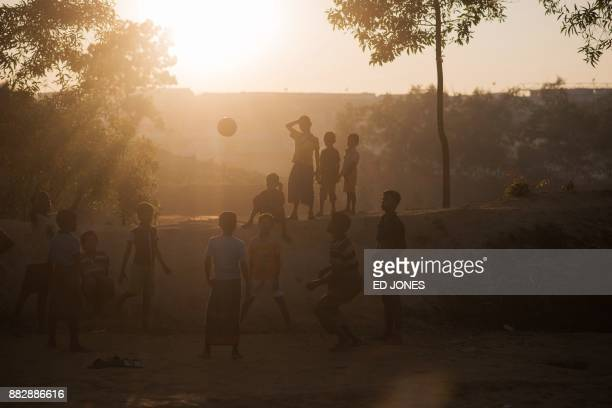 TOPSHOT Rohingya migrant children play football at the Kutupalong refugee camp at Cox's Bazar on November 30 2017 Rohingya are still fleeing into...