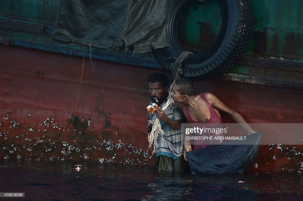 A Rohingya migrant eats food dropped by a Thai army helicopter after he jumped to collect the supplies at sea from a boat drifting in Thai waters off the southern island of Koh Lipe in the Andaman sea on May 14, 2015. A boat crammed with scores of Rohingya migrants -- including many young children -- was found drifting in Thai waters on May 14, with passengers saying several people had died over the last few days. AFP PHOTO / Christophe ARCHAMBAULT / AFP / CHRISTOPHE