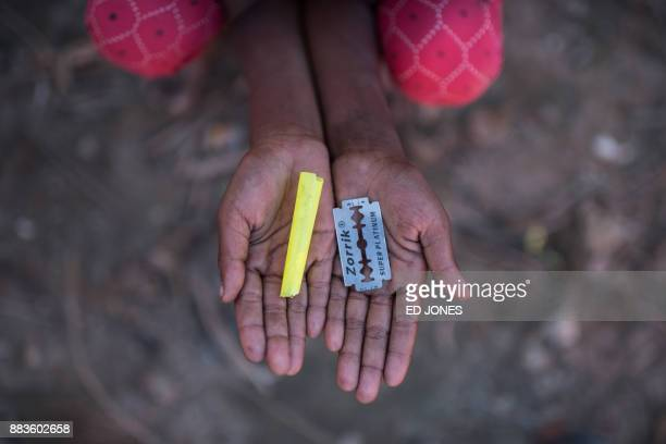 TOPSHOT Rohingya migrant girl Halima Khatun who arrived in Bangladesh in October holds a whistle and a razor blade that she uses as toys at the...