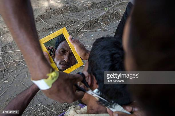Rohingya migrant helps cut his friend's hair at a temporary shelter on May 19 2015 in Kuala Langsa Aceh province Indonesia Hundreds of Myanmar's...