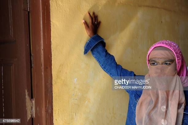 A Rohingya migrant woman from Myanmar stands at the entrance of a living quarters during a visit by US Assistant Secretary of State Anne Richard at...