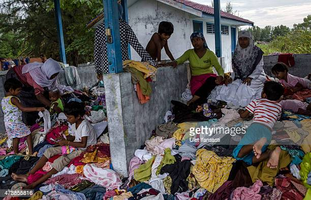 Rohingya migrant women collect used clothes at a temporary shelter on May 18 2015 in Kuala Langsa Aceh province Indonesia Hundreds of Myanmar's...