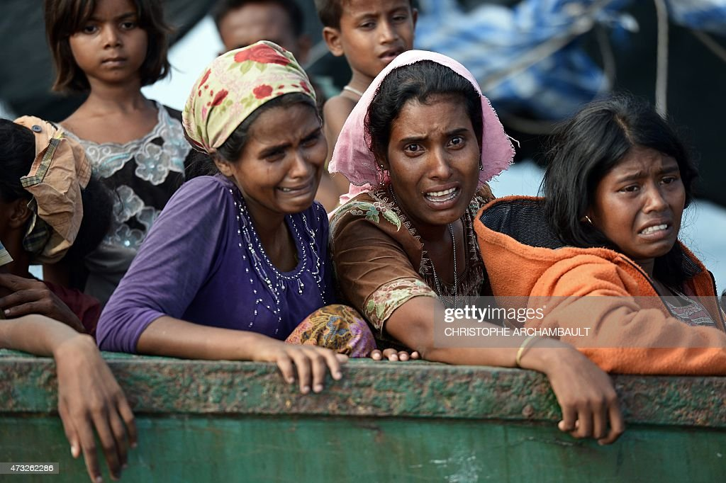 Rohingya migrant women cry as they sit on a boat drifting in Thai waters off the southern island of Koh Lipe in the Andaman sea on May 14, 2015. The boat crammed with scores of Rohingya migrants -- including many young children -- was found drifting in Thai waters on May 14, according to an AFP reporter at the scene, with passengers saying several people had died over the last few days. AFP PHOTO / Christophe ARCHAMBAULT