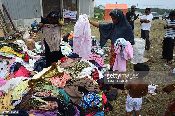 Rohingya migrants from Myanmar search through clothes donated by residents at the new confinement area in the fishing town of Kuala Langsa in Aceh...