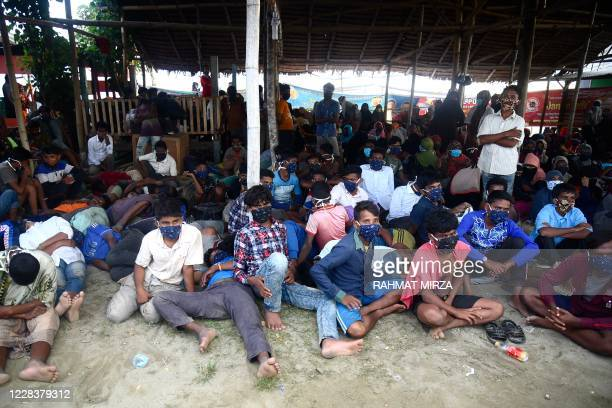 Rohingya migrants look on following their arrival by boat in Lhokseumawe, Aceh on September 7, 2020. - Nearly 300 Rohingya migrants came ashore on...