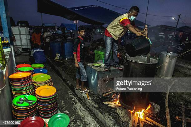 Rohingya migrants seen cooking at the makeshift camp on May 18 2015 in Kuala Langsa Indonesia Malaysia said on Sunday that its foreign minister would...