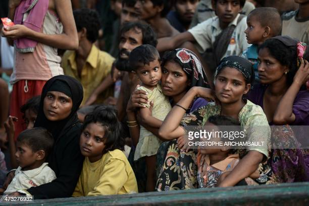 Rohingya migrants sit on a boat drifting in Thai waters off the southern island of Koh Lipe in the Andaman sea on May 14 2015 A boat crammed with...