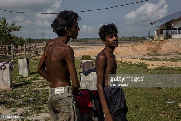 Rohingya migrants stand after arriving at the port in Julok village on May 20 2015 in Kuta Binje Aceh Province Indonesia Hundreds of Myanmar's...