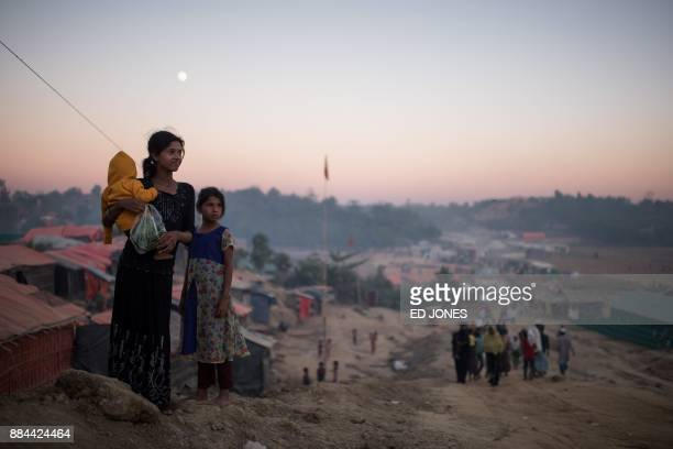 TOPSHOT Rohingya migrants stand along a track running through the Thankhali refugee camp in Cox's Bazar on December 2 2017 Rohingya are still fleeing...