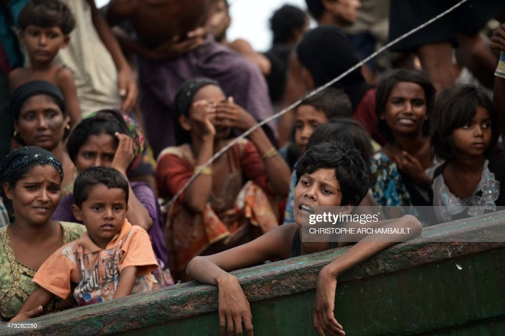 Rohingya migrants stand and sit on a boat drifting in Thai waters off the southern island of Koh Lipe in the Andaman sea on May 14, 2015. The boat crammed with scores of Rohingya migrants -- including many young children -- was found drifting in Thai waters on May 14, according to an AFP reporter at the scene, with passengers saying several people had died over the last few days. AFP PHOTO / Christophe ARCHAMBAULT