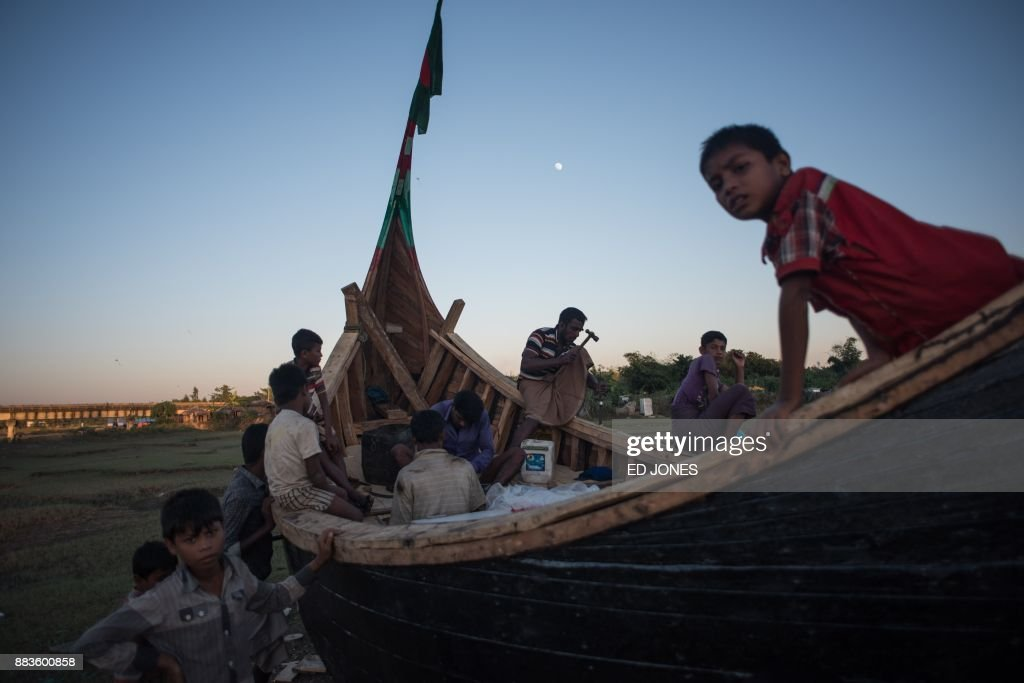 Rohingya migrants work on a boat at the Shamlapur refugee camp in Cox's Bazar on December 1, 2017. Rohingya are still fleeing into Bangladesh even after an agreement was signed with Myanmar to repatriate hundreds of thousands of the Muslim minority displaced along the border, officials said on November 27. / AFP PHOTO / Ed JONES