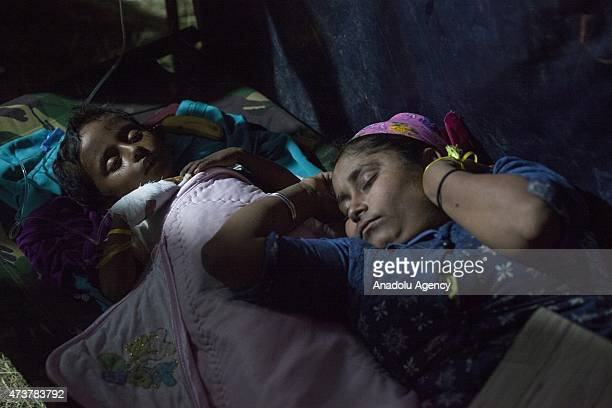 Rohingya mother and child sleep in a temporary medical clinic after receiving medical aid, in Kuala Langsa Port in Langsa, Aceh province, Indonesia...