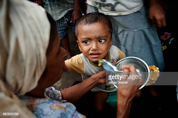 Rohingya mother from Aung Mingarlar village of Sittwe feeds her baby with the small amounts of food they have Located in Aung Mingalar remains the...