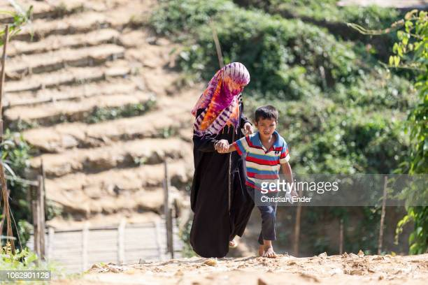 Kutupalong Ukhiya near Cox´s Bazar Bangladesh October 15 2018 A Rohingya mother in a niqab in the camp with her boy walking on a path Refugee camp of...