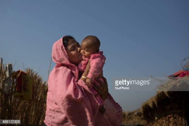 A Rohingya mother kisses her new born baby at Kutupalong Refugee Camp Cox's Bazar Bangladesh on February 13 2017 After attacks by Rohingya militants...