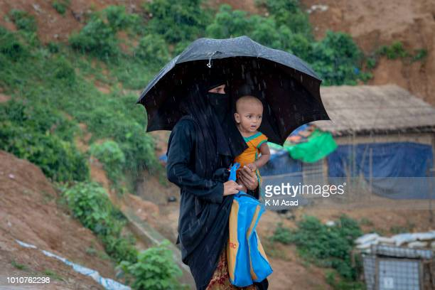 A Rohingya mother with her child walk in the heavy rain at Balukhali Rohingya Refugee camp in Teknaf Cox's Bazar