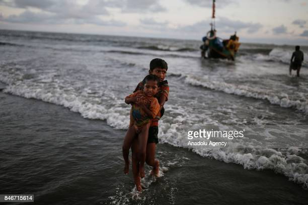 COX'S BAZAR BANGLADESH SEPTEMBER 13 A Rohingya Muslim boy fled from ongoing military operations in Myanmars Rakhine state carries a child after...