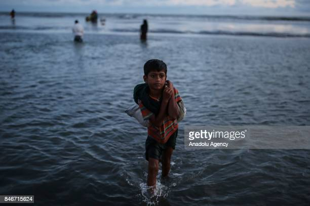 COX'S BAZAR BANGLADESH SEPTEMBER 13 A Rohingya Muslim boy fled from ongoing military operations in Myanmars Rakhine state carries his stuff on his...