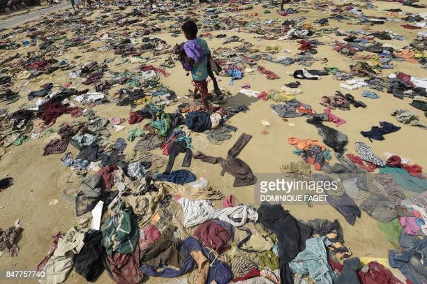 Rohingya Muslim boy walks past discarded clothing on the ground at the Bhalukali refugee camp near Ukhia on September 16 2017 According to the UN...