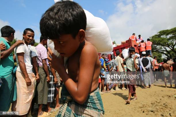 Rohingya Muslim child, fled from ongoing military operations in Myanmars Rakhine state, carries a bag of humanitarian aid at a makeshift camp in...