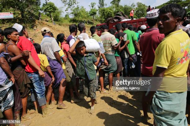 Rohingya Muslim child, fled from ongoing military operations in Myanmars Rakhine state, carries a bag of humanitarian aid as others stand in line at...