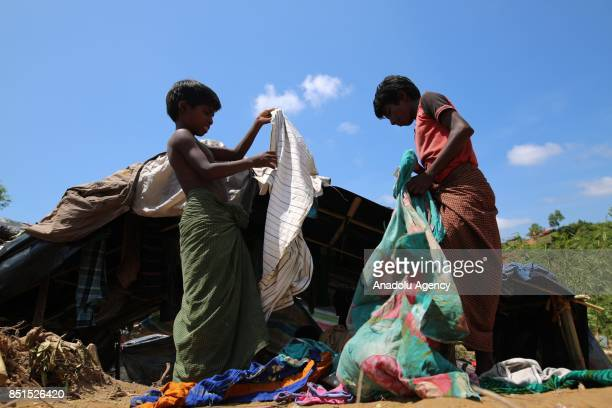 Rohingya Muslim children, fled from ongoing military operations in Myanmars Rakhine state, search usable clothes near a tent at a makeshift camp in...