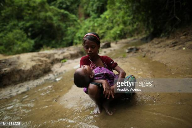 COX'S BAZAR BANGLADESH SEPTEMBER 08 A Rohingya Muslim girl fled from ongoing military operations in Myanmars Rakhine state sits in a small stream...