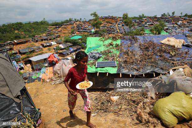 Rohingya Muslim girl, fled from ongoing military operations in Myanmars Rakhine state, carries a plate of food at a makeshift camp in Teknaff,...