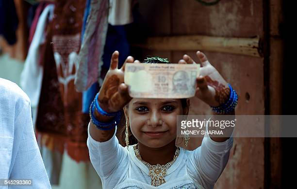 Rohingya muslim girl Roshida holds up a ten rupee not which she received as a gift for Eid alFitr celebration at a slum in New Delhi on July 7 2016...