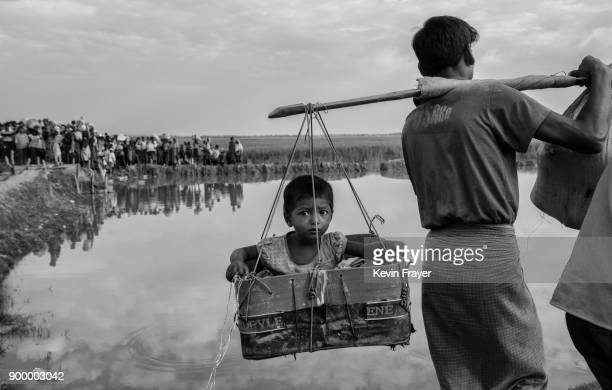 COX'S BAZAR BANGLADESH NOVEMBER 02 A Rohingya Muslim refugee boy is carried in a basket after crossing the border from Myanmar into Bangladesh close...