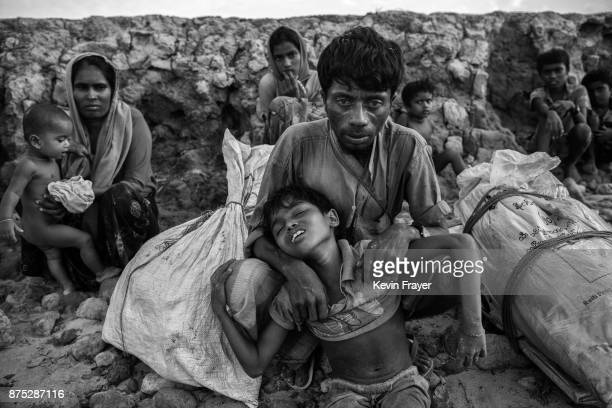 COX'S BAZAR BANGLADESH OCTOBER 30 A Rohingya Muslim refugee boy is held by his father after arriving by boat to Shah Porir Dwip on October 30 2017...