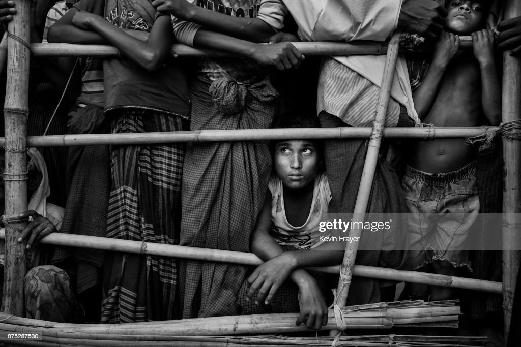 COX'S BAZAR, BANGLADESH - OCTOBER 24: A Rohingya Muslim refugee boy waits with others to receive food aid from a local NGO on October 24, 2017 at the Kutupalong refugee camp in Cox's Bazar, Bangladesh. More than 600,000 Rohingya refugees have flooded into Bangladesh to flee an offensive by Myanmar's military that the United Nations has called 'a textbook example of ethnic cleansing'. The refugee population continues to swell further, with thousands more Rohingya Muslims making the perilous journey on foot toward the border, or paying smugglers to take them across by water in wooden boats. Hundreds are known to have died trying to escape, and survivors arrive with horrifying accounts of villages burned, women raped, and scores killed in the 'clearance operations' by Myanmar's army and Buddhist mobs that were sparked by militant attacks on security posts in Rakhine state on August 25, 2017. What the Rohingya refugees flee to is a different kind of suffering in sprawling makeshift camps rife with fears of malnutrition, cholera, and other diseases. Aid organizations are struggling to keep pace with the scale of need and the staggering number of them - an estimated 60 percent - who are children arriving alone. Bangladesh, whose acceptance of the refugees has been praised by humanitarian officials for saving lives, has urged the creation of an internationally-recognized 'safe zone' where refugees can return, though Rohingya Muslims have long been persecuted in predominantly Buddhist Myanmar. World leaders are still debating how to confront the country and its de facto leader, Aung San Suu Kyi, a Nobel Peace Prize laureate who championed democracy, but now appears unable or unwilling to stop the army's brutal crackdown. During a recent visit to Myanmar, U.S Secretary of State Rex Tillerson called for a 'credible' probe into human rights violations against the Rohingya but said he would advise against full sanctions on the country.