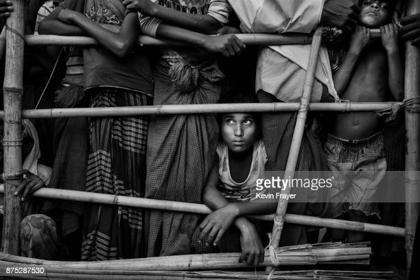 COX'S BAZAR BANGLADESH OCTOBER 24 A Rohingya Muslim refugee boy waits with others to receive food aid from a local NGO on October 24 2017 at the...