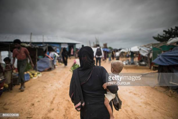 Rohingya Muslim refugee carries a child through Kutupalong refugee camp in the Bangladeshi district of Ukhia on September 28 2017 The UN has drawn up...