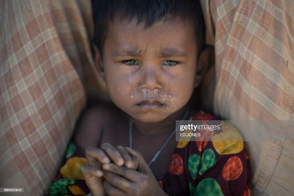 Rohingya Muslim refugee child cries as she sits in the Kutupalong refugee camp in Cox's Bazar on December 4, 2017. Rohingya are still fleeing into Bangladesh even after an agreement was signed with Myanmar to repatriate hundreds of thousands of the Muslim minority displaced along the border, officials said on November 27. / AFP PHOTO / Ed JONES