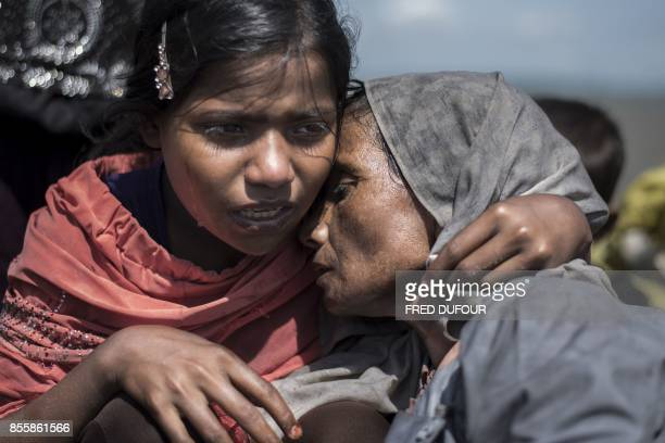 TOPSHOT Rohingya Muslim refugee cries with her mother on the Bangladeshi shoreline of the Naf river after crossing the border from Myanmar in Teknaf...