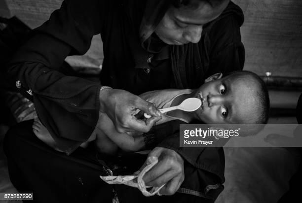 COX'S BAZAR BANGLADESH OCTOBER 25 Rohingya Muslim refugee Hamida Khatun feeds her malnourished one yearold son Ibrahim high calorie peanut paste at a...